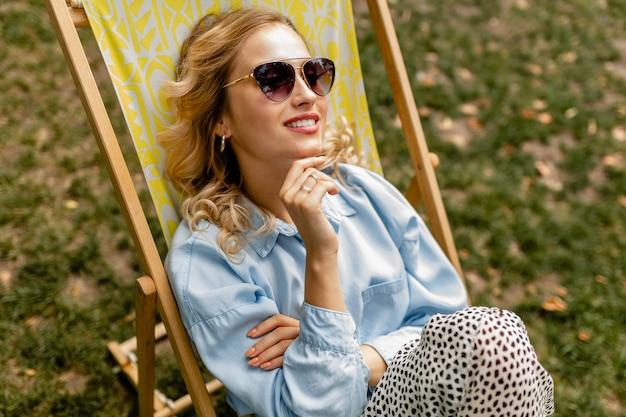 Привлекательная блондинка улыбается женщина сидит расслабленно в шезлонге в стильной одежде