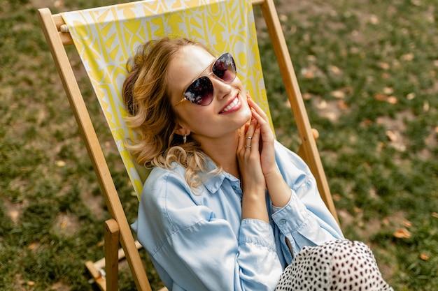 세련된 복장에 갑판 의자에 편안하게 앉아 매력적인 금발 웃는 여자