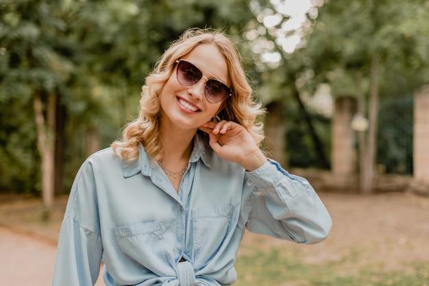 スタイリッシュな衣装で公園を歩く魅力的な金髪の笑顔の女性