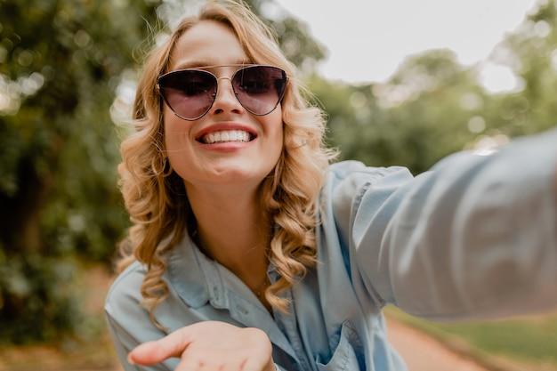 Привлекательная белокурая улыбающаяся женщина гуляет в парке в летнем наряде, делающем селфи на телефоне