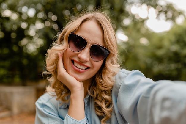 電話でselfie写真を撮る夏の衣装で公園を歩く魅力的な金髪の笑顔の女性