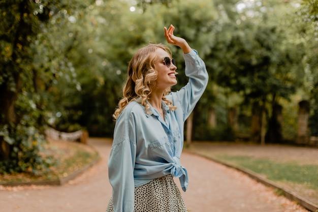 夏の衣装で公園を歩く魅力的な金髪の笑顔の女性