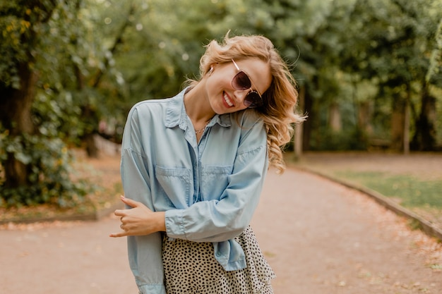 Attractive blond smiling woman walking in park in stylish outfit