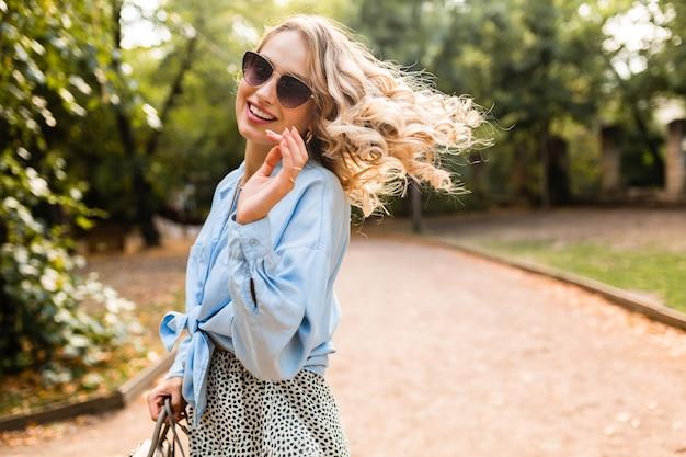 Attraente donna bionda sorridente che cammina nel parco in abito estivo camicia blu e gonna, indossando occhiali da sole eleganti e borsetta, stile di moda di strada, stato d'animo felice