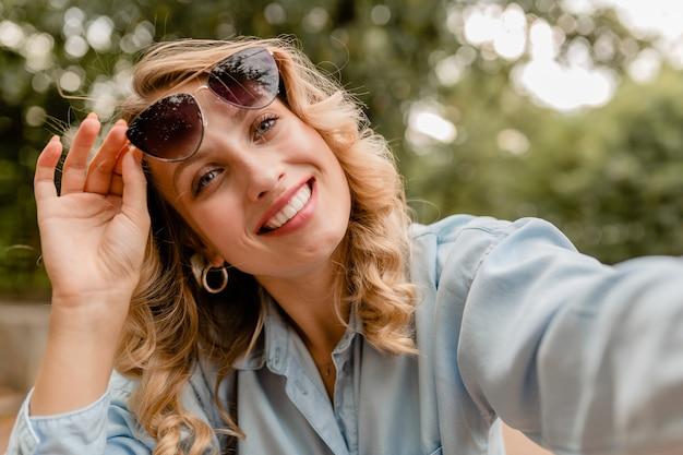 Attraente donna bionda sorridente che cammina nel parco in abito estivo prendendo foto selfie sul telefono