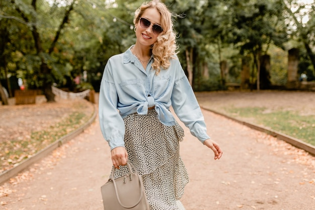 Attractive blond smiling woman walking in park in summer outfit