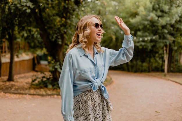 夏の衣装で公園を歩いて手を振って魅力的な金髪の笑顔の女性こんにちは