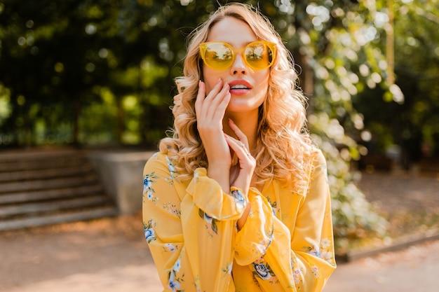 Donna sorridente alla moda bionda attraente in occhiali da sole d'uso della camicetta gialla
