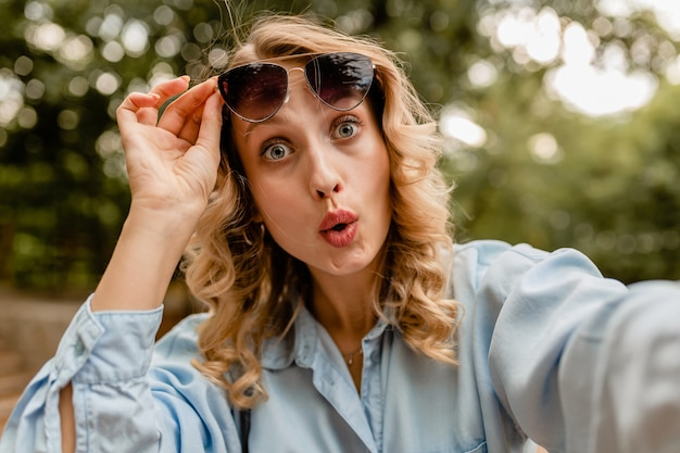 Attraente bionda sorpresa divertente donna in abito estivo che cattura foto selfie sul telefono