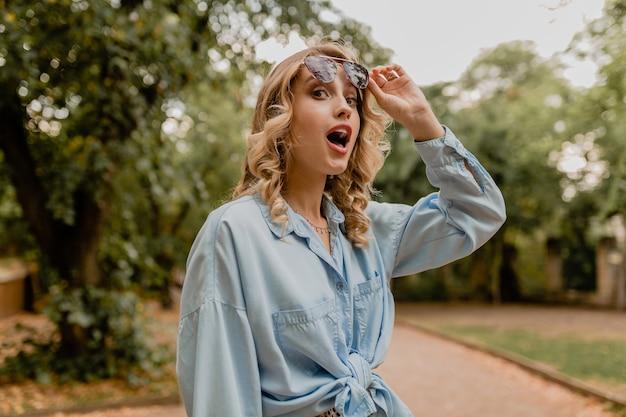 Привлекательная блондинка удивлена женщина гуляет в парке в летнем наряде