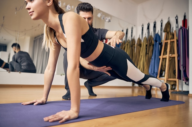Attractive blond with fit body working out in yoga class while experienced instructor showing her correct pose