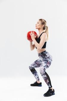 운동복을 입은 20대 매력적인 금발 여성이 흰 벽에 격리된 에어로빅을 하는 동안 피트니스 공으로 운동을 하고 있습니다.
