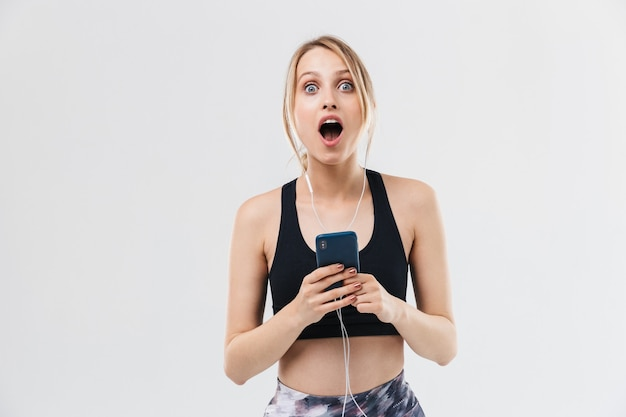 白い壁に隔離されたジムでのフィットネス中にワークアウトとスマートフォンで音楽を聴くスポーツウェアに身を包んだ魅力的な金髪の女性