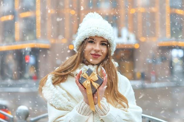 降雪時の降雪時に通りでギフトボックスを保持している白いコートの魅力的なブロンドの女性。テキスト用のスペース