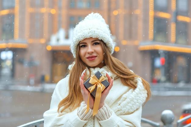 降雪時に通りでギフトボックスを保持している白いコートの魅力的なブロンドの女性。テキスト用のスペース