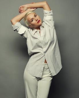 Привлекательная блондинка женщина на сером фоне