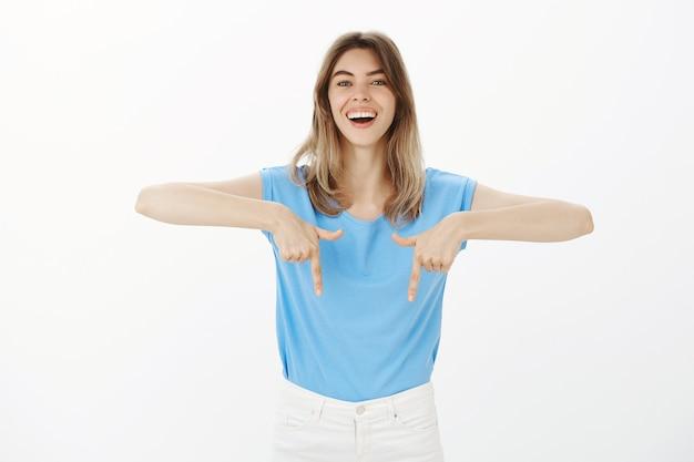 배너에서 아래로 손가락을 가리키는 광고를 보여주는 매력적인 금발 여자