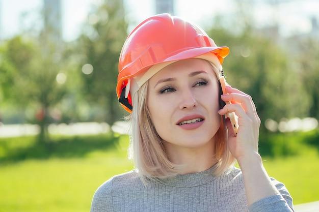緑の芝生の背景に公園でオレンジ色のヘルメットの魅力的な金髪のボスの女性ビルダー。