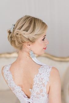 Привлекательная блондинка невеста стоит у окна в белом интерьере в винтажном стиле.