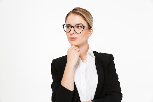 Attractive blonde business woman in eyeglasses holding hand near chin and looking away over white