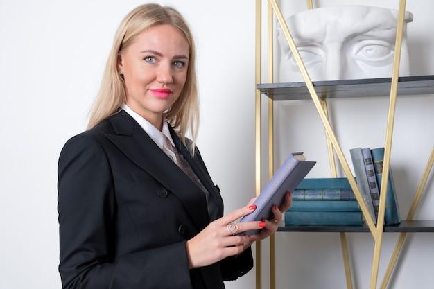ビジネススーツを着た魅力的な金髪のビジネスウーマンが本棚に立って、読む本を選ぶ