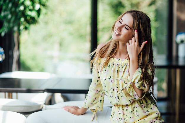 魅力的な金髪の白人女性、カフェテラスで休んで楽しみにモデル