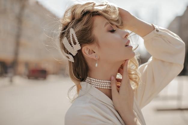 진주 목걸이와 세련된 흰색 블라우스에 매력적인 금발 곱슬 아가씨가 부드럽게 머리카락을 만지고 외부 포즈를 취합니다.