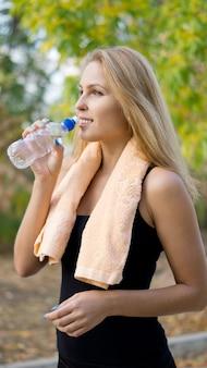 Привлекательная блондинка спортсменка пьет воду в бутылках для гидратации после тренировки в парке, делая упражнения