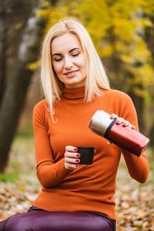 明るい服を着た魅力的な金髪の女性は、金属の魔法瓶を開き、秋の背景にお茶、カップにコーヒーを注ぐ