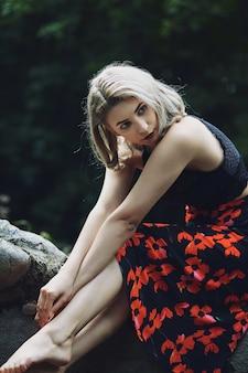 Привлекательная блондинка с цветочным платьем сидит в лесу