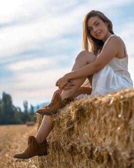 ヘイリックに座ってカメラに向かってポーズをとって白いシャツを着た魅力的な金髪の女性