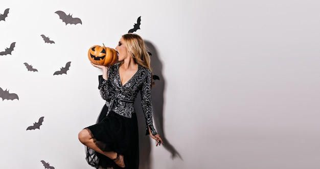 Attractive blonde girl eating halloween pumpkin.  inspired young woman posing in witch attire.