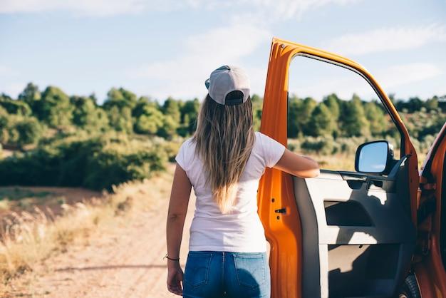 Привлекательная белокурая девушка сзади держа оранжевую автомобильную дверь на открытом воздухе