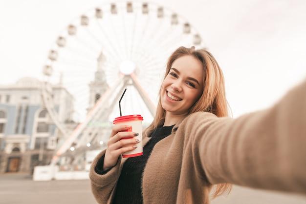 Привлекательная блондинка в повседневной одежде, надев пальто, держит в руках чашку кофе, снимает селфи, смотрит в камеру