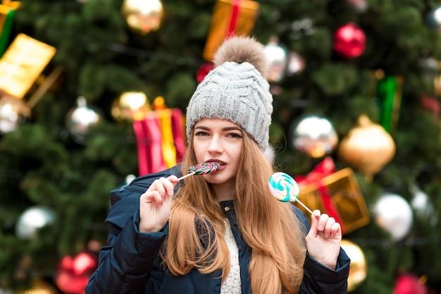 トウヒの背景でカラフルなクリスマスのお菓子を食べるニットの暖かい帽子の魅力的なブロンドの女の子