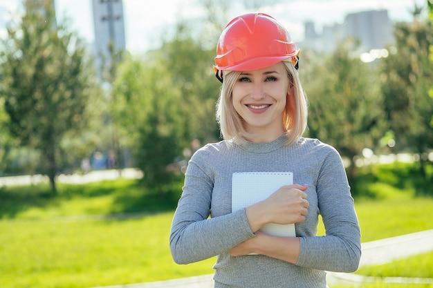 주황색 헬멧을 쓴 매력적인 금발 소녀 조경 디자이너는 푸른 잔디 배경에 있는 공원에서 메모가 적힌 공책을 들고 있습니다.