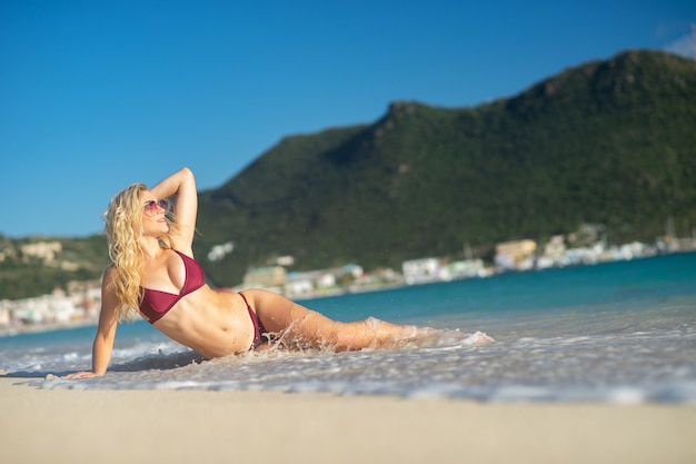Attractive blonde girl lying down on the beach, fit sporty healthy sexy body in bikini, woman enjoys sun, freedom, vacation, summertime fun concept.