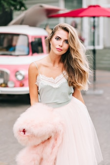 通りのチュールスカートに長い髪の魅力的なブロンドの女の子。彼女はカメラに目を向けます。