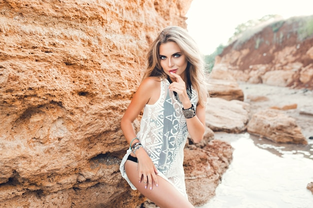Attractive blonde girl with long hair is posing to the camera on rocks background. she is touching bode and looks to the camera.