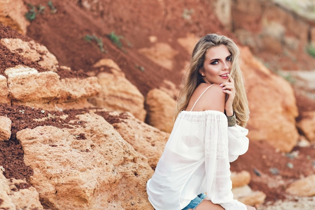 長い髪の魅力的なブロンドの女の子が岩の背景にカメラにポーズをとっています。彼女はカメラに微笑んでいます。