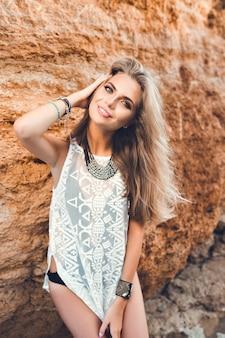 長い髪を持つ魅力的なブロンドの女の子は、岩の背景にカメラにポーズをとっています。彼女は微笑んでいる。