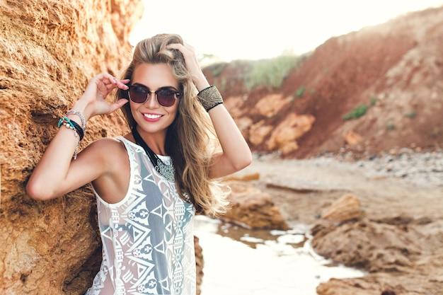 長い髪の魅力的なブロンドの女の子は、岩の背景にカメラにポーズをとっています。彼女は髪に触れて笑っています。