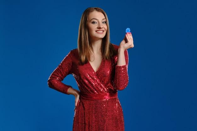 Привлекательная блондинка с макияжем, в красном платье с пайетками показывает одну фишку, улыбается и смотрит на нее, положив руку на бедро, позирует на синем фоне. азартные развлечения, покер, казино. крупный план.