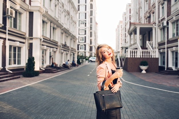 通りにコーラルジャケットのコーヒーカップと歩いてほのかの唇と魅力的なブロンドの女の子。彼女は黒いバッグを着ています