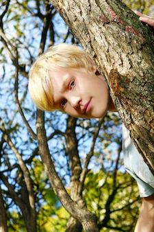 Attractive blonde guy behind a tree