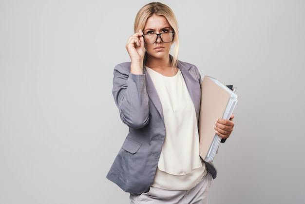 Attractive blonde haired businesswoman wearing jacket standing isolated over gray wall, carrying folders