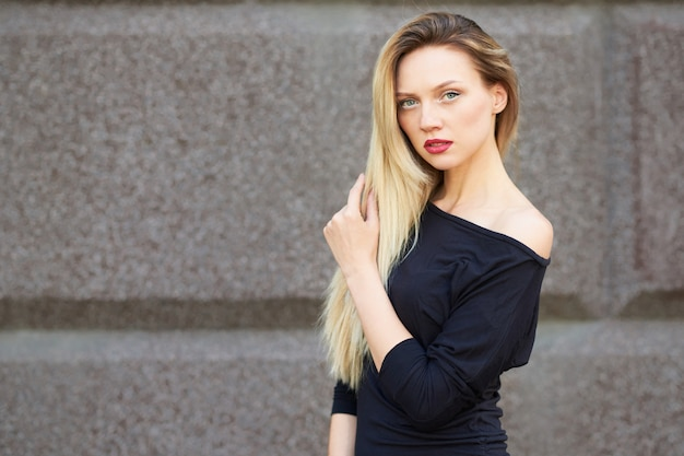 黒のドレスを着た魅力的なブロンド。完全に成長しています。彼は女性的な歩き方で歩きます。石垣を背景に。あらゆる目的のために。