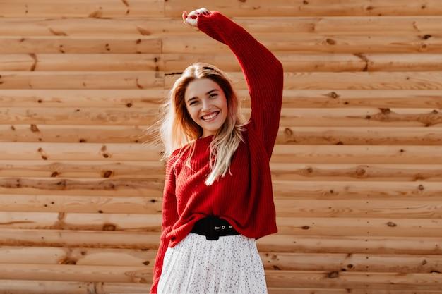 야외 좋은 시간을 보내고 아름 다운 빨간 스웨터에 매력적인 금발. 나무 벽에 행복 하 게 포즈를 취하는 젊은 여자를 웃 고.