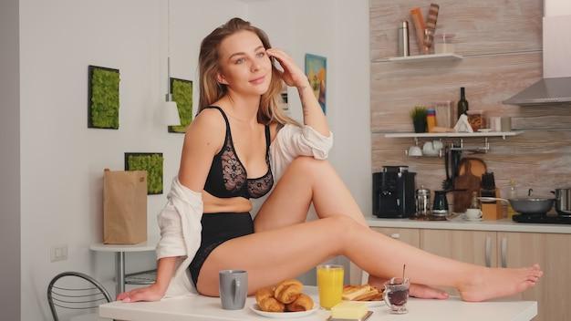 朝食時に台所のテーブルに横たわっている電話を使用して魅惑的な下着の魅力的なブロンドの女性。黒のランジェリーを身に着けている笑顔をリラックスして入れ墨の屈託のないセクシーな若い女性