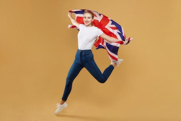 Привлекательная блондинка прыгнула с британским флагом. фотосессия в студии с желтым фоном.